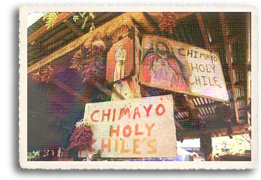 A stand in Chimayó sells Chimayo chile ristras, fruit and retablos. A sign proclaims the chiles are holy.