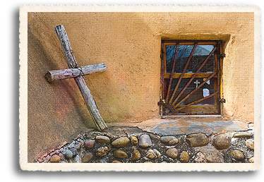 In Chimayó, New Mexico, a handmade cross sits in the corner of a traditional adobe style mission chapel, the Santuario de Chimayo. inside the window is the Sacristy, where pilgrims to the santuario leave rosaries, crutches, gifts and photos as evidence of healing.