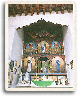 The altar at the church of San Jose de Gracia at Las Trampas showing the whitewashed walls. The altar itself is surrounded by retablos and santos made by local santeros.